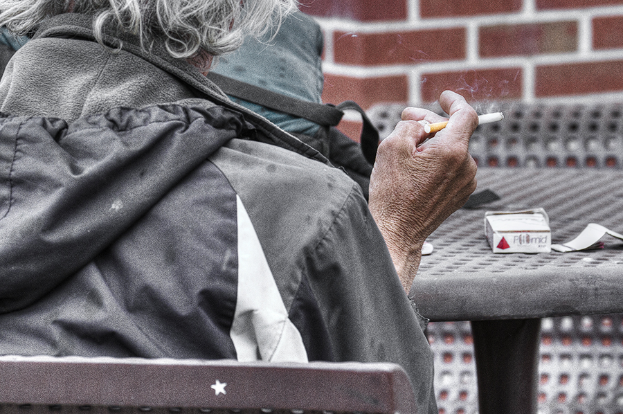 A man smokes a Pyramid cigarette amid falling raindrops in downtown Golden, Colo.