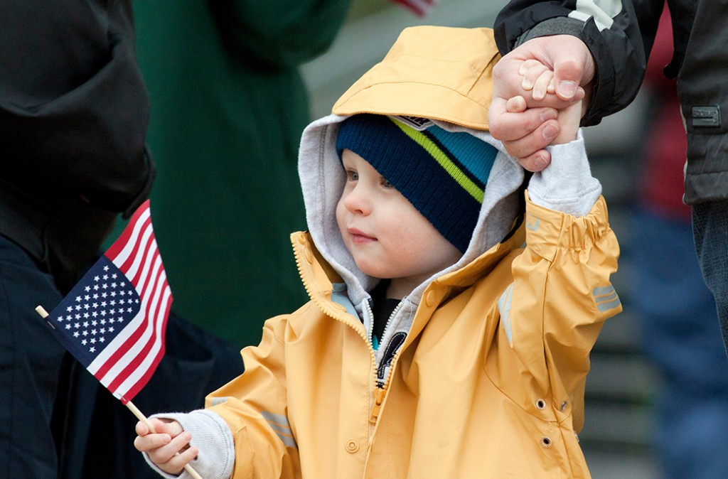 Dax Helgeson, 2, of Thornton, clutches his father's finger in one hand while waving an American flag in the other Saturday morning at the Westminster Armed Forces Tribute Garden Ceremony.