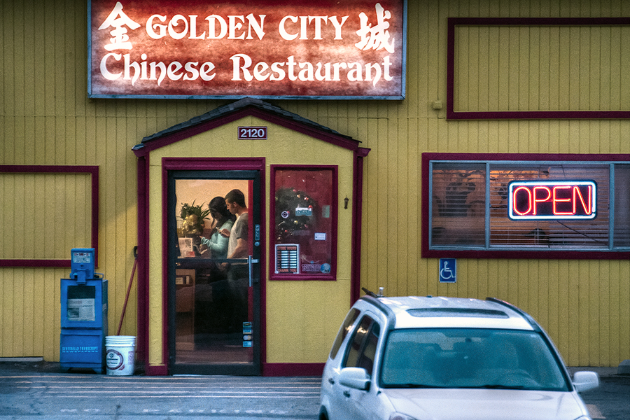A couple pays their tab after dining out at the Golden City Chinese Restaurant in Golden, Colo. For a twilight scene such as this, white balance can be difficult to get correct without manual adjustment.