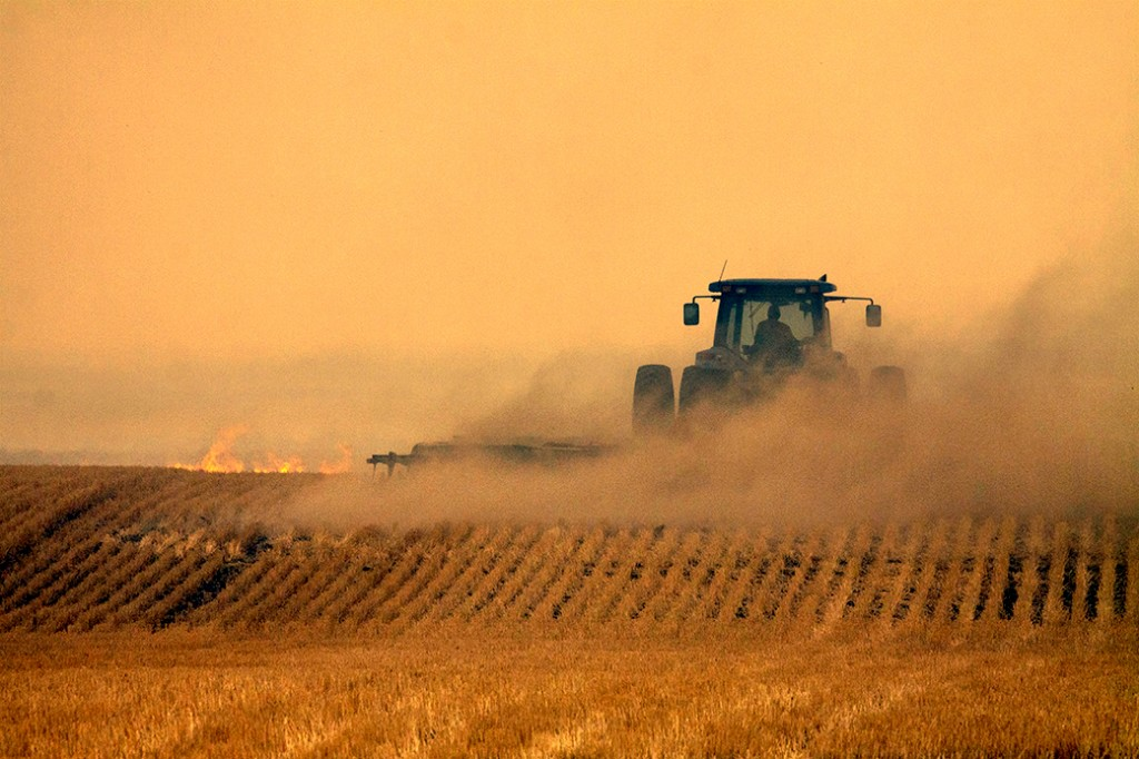 A man operates a tractor through a section of wheat fields in order to douse flames Aug. 30, 2012 in rural Dawes County.