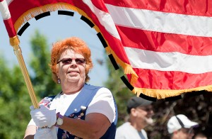 """An """"S"""" curve forms as the flag held by Marg Watters, of Arvada, billows in the wind during the 2012 Glenn Close Memorial Day Parade in Arvada, Colo."""