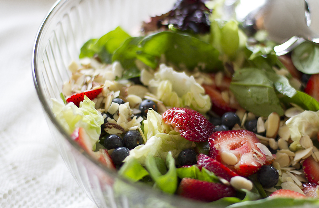 A mixed greens salad, sprinkled with almond slices and boasting blueberries and strawberries, provides a wonderful blend of taste and texture.