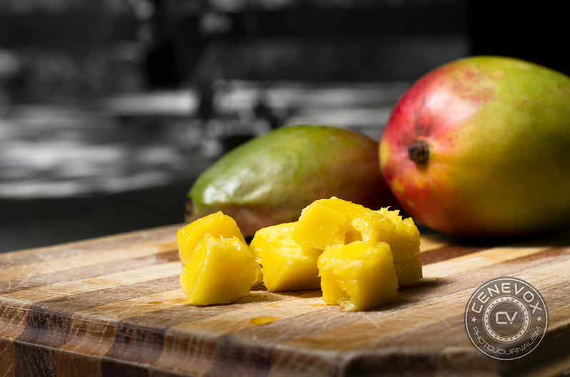 Several sliced mango pieces lie in front of two other mangos atop a wooden cutting board.