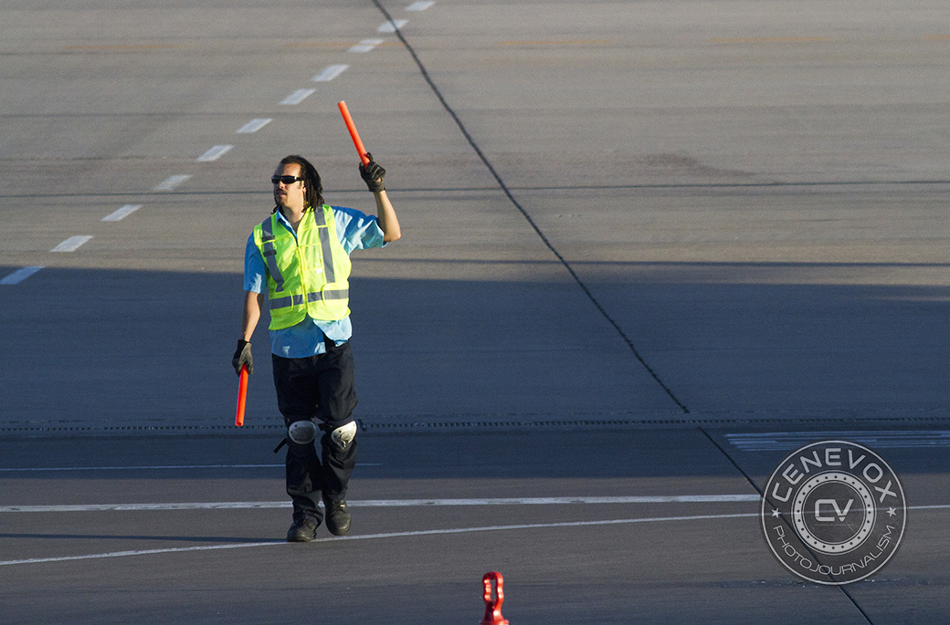 A United Airlines employee directs a plane to a gate at Denver International Airport's Concourse B.
