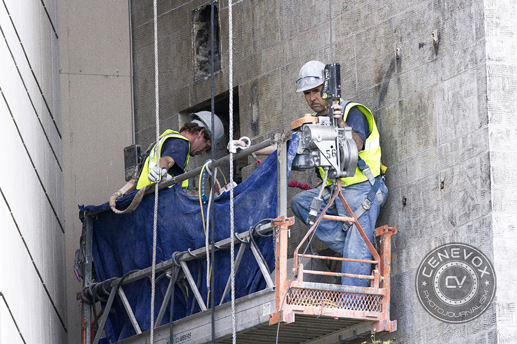 Two construction workers descend from the side of a building on a lift platform adjacent Lake Shore Drive in Chicago.