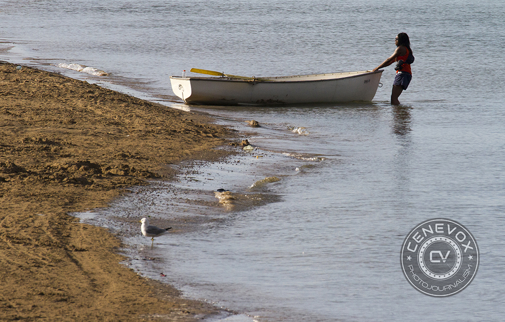 A woman hauls a rowboat into the waters of Lake Michigan in Chicago during the summer of 2013.
