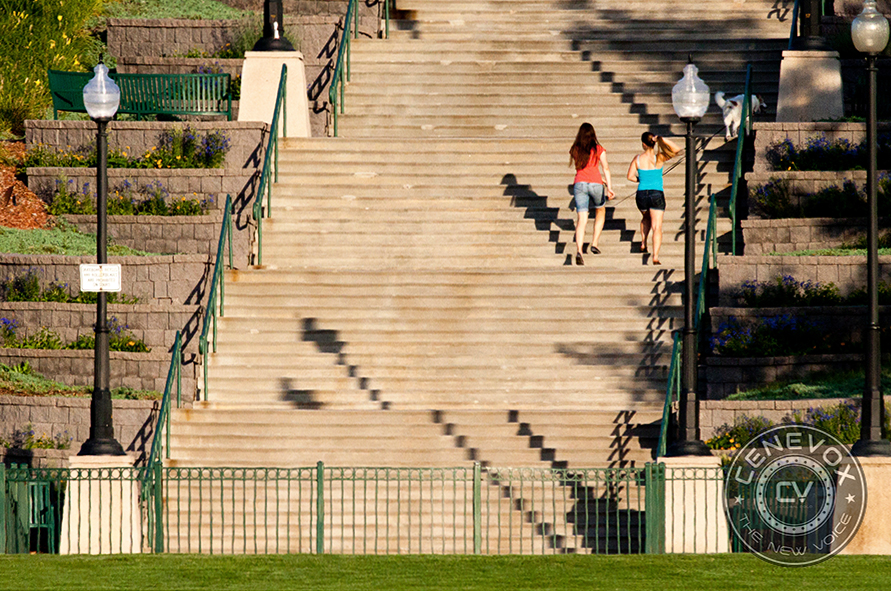 """Two passersby climb the 99 stairs in Westminster's City Park prior to the start of """"Puss in Boots,"""" one of a series of movies exhibited during the summer of 2012 sponsored by local companies and the city of Westminster. Metadata: f/11; 1/1000; ISO 1000; 400mm focal length"""