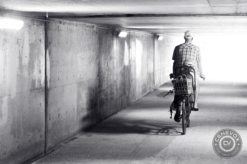 A father and his daughter ride through an underpass in Columbia, Mo.