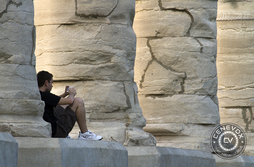 A man uses a digital camera while sitting at the base of one of the six ionic columns dominating the University of Missouri-Columbia's Francis Quadrangle.