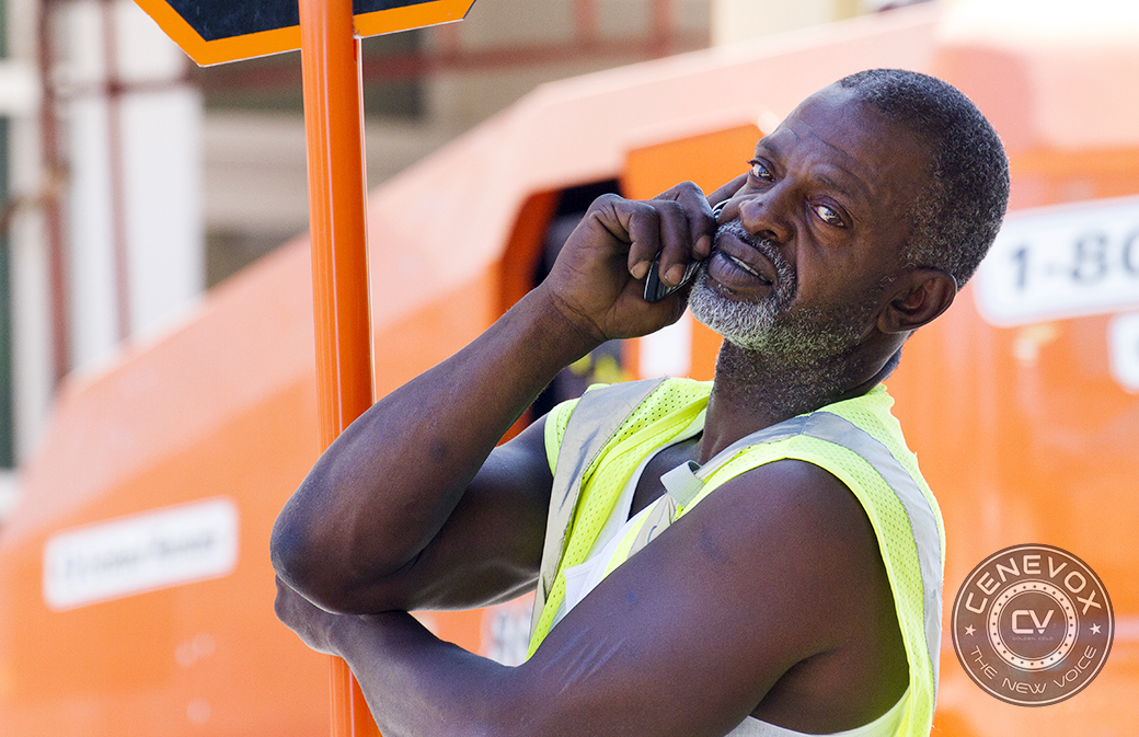 A man talks on his cell phone while directing traffic through a construction site in Columbia, Mo.