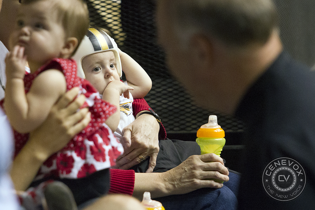 Held by Lois Stueve, of Macon, Graham Rogh, 1, of Columbia, wears an MU helmet Sept. 20, 2013 at the Hearnes Center during a women's volleyball match between the MU Tigers and the Towson Tigers.