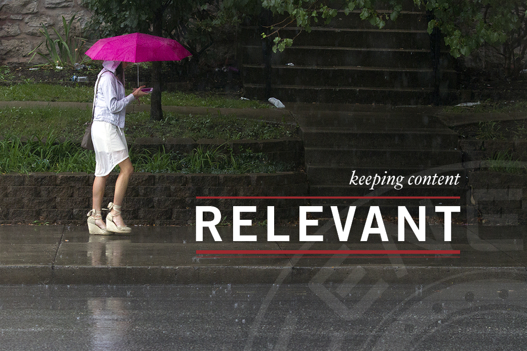A woman holds a fuchsia umbrella in one hand and her cell phone in the other during a rainy day in Columbia, Mo.