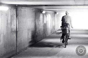 A father and his daughter ride through an underpass Aug. 5, 2013 in Columbia, Mo.