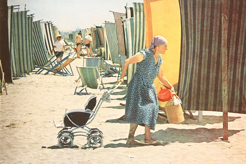 """Crowded Beach at Rimini, on the northern Adriatic, sparkles all summer long with multi-colored windbreaks and low-slung canvas chairs. The close-knit Italian family invariably takes the baby along."" Appeared in the 1961 LIFE World Library's ""Italy"" book. No photographer credit given."