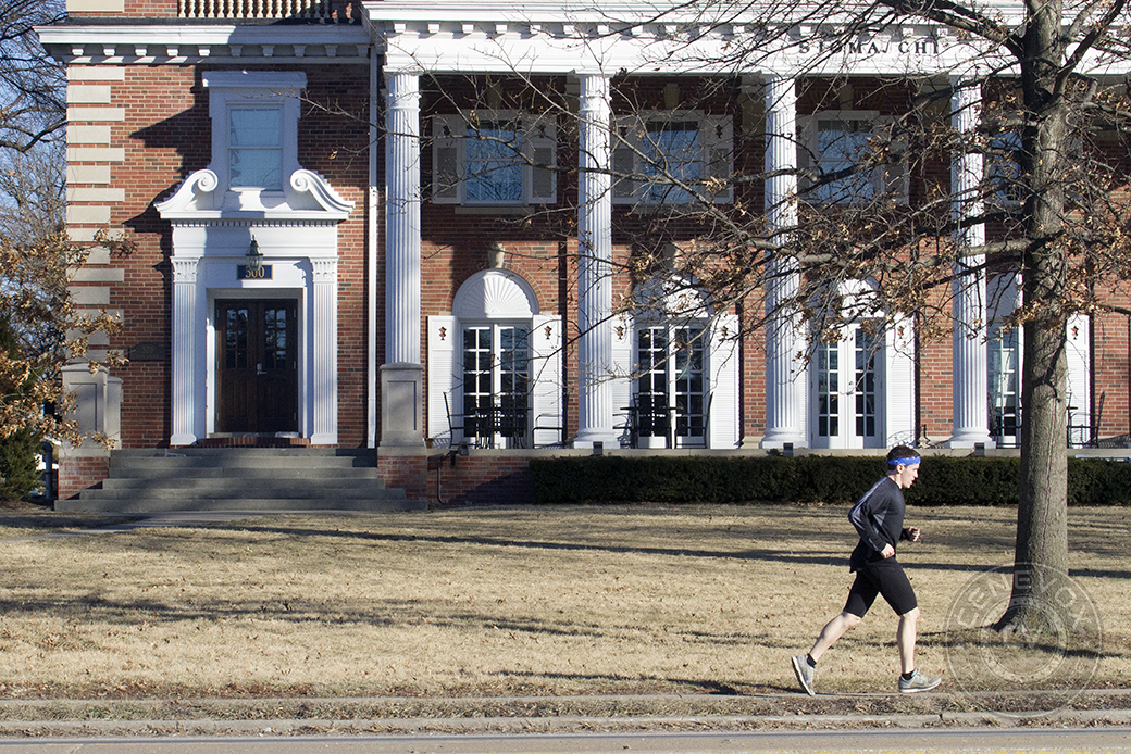 A man wearing a blue bandana jogs along South College Avenue, past the Sigma Chi house at the University of Missouri.