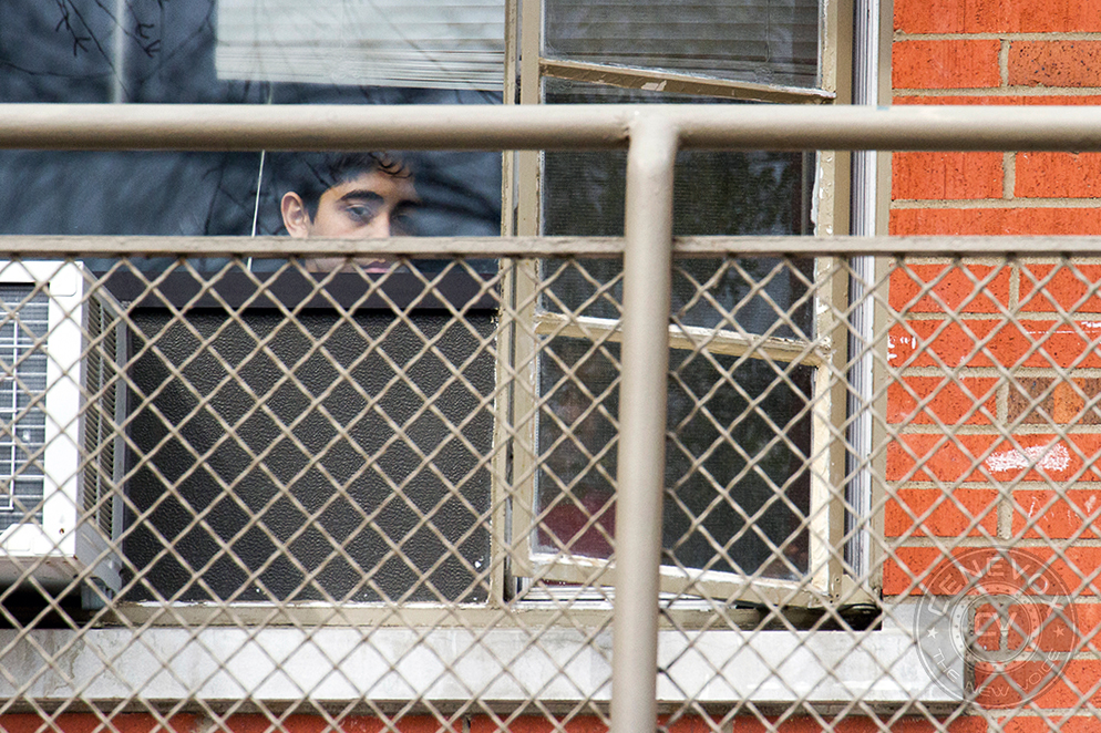 A boy looks out from his second-story apartment as MU Campus Facilities employees renovate exterior walkways at University Village student housing complex.