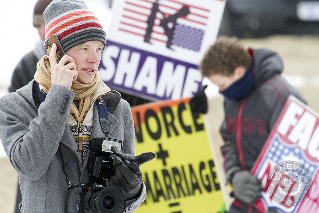 A man talks on his iPhone while protesters from the Westboro Baptist Church picket in the background.