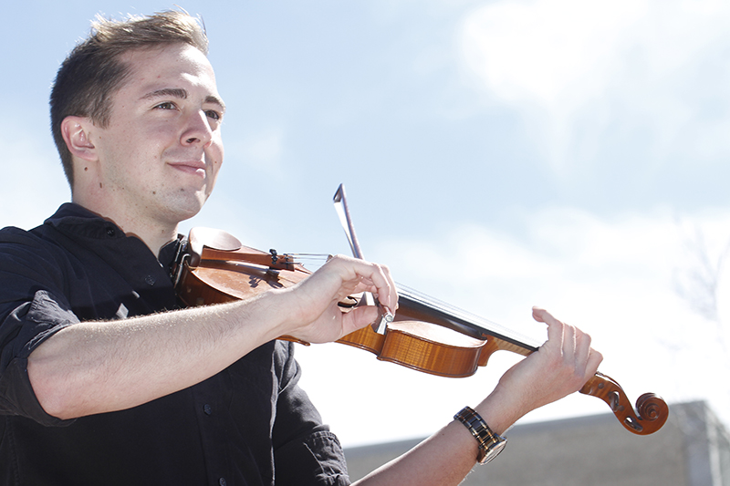 """University of Missouri undergraduate Dominic Chambers fiddles to Avicii's """"Wake Me Up"""" Friday afternoon at Speaker's Circle. Chambers is a nursing major and is part of the MU Celtic Club."""
