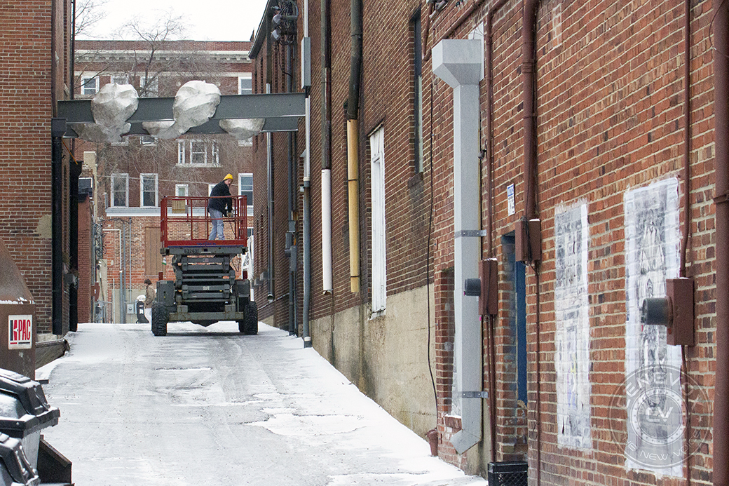 A man operates a scissor lift in the alley between East Broadway and Cherry Streets in Columbia, Mo.