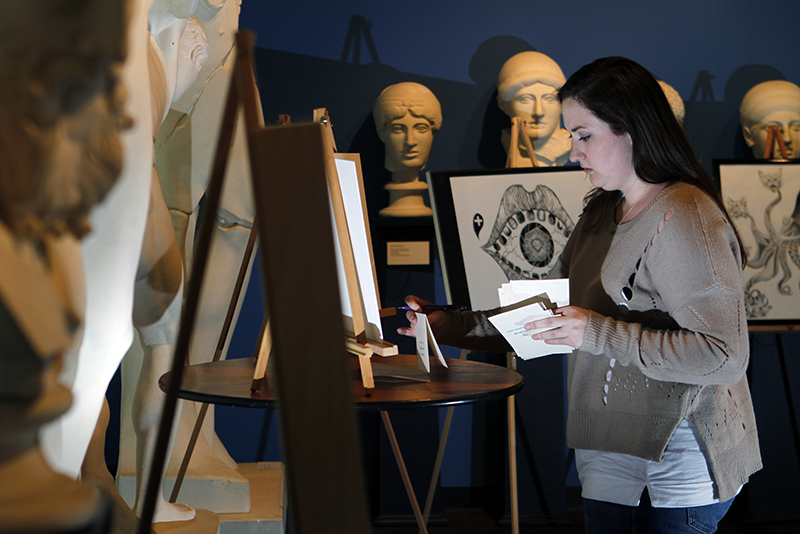 """MU senior Tara Meyer, co-president of the Museum Advisory Council of Students, arranges artwork captions for the """"Art After Dark"""" event hosted at Mizzou North."""
