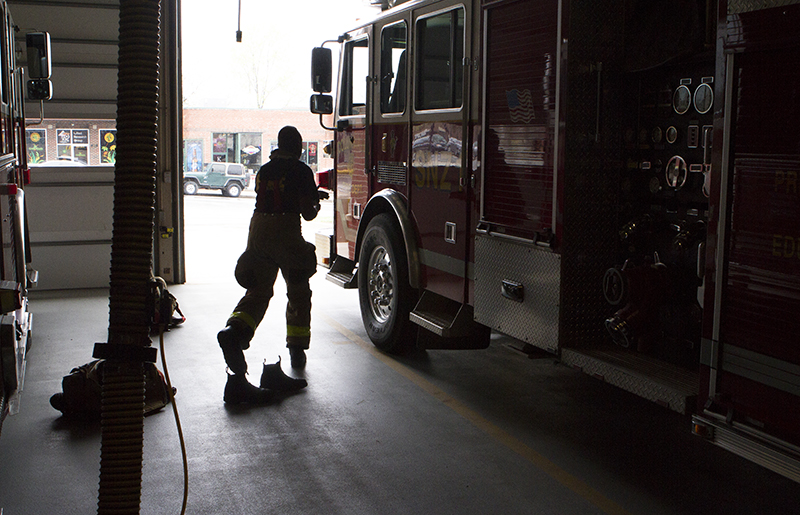 Columbia Firefighter Dale Turner grabs his gear before responding to a fire alarm at the University of Missouri's Gaines/Oldham Black Culture Center.