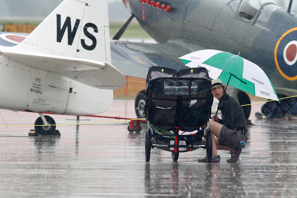 Catalin Giacchi huddles by her children at the 2014 Salute to Veterans Airshow on Saturday at Columbia Regional Airport. Rain fell throughout the day and delayed some of the planned events.