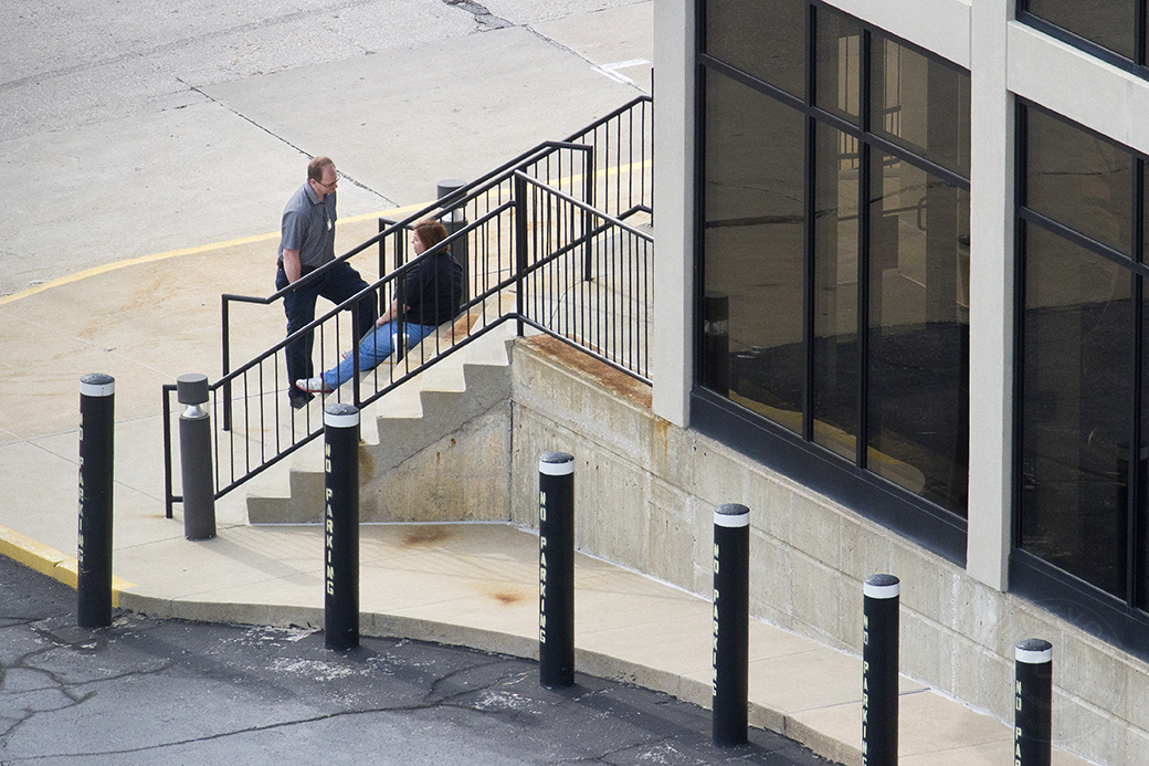 Two Columbia Daily Tribune employees chat outside the newspaper's offices at 100 N 4th St. in Columbia, Mo.