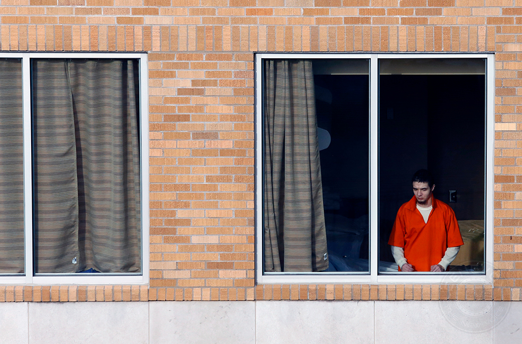 A patient at the Missouri Psychiatric Center watches pedestrians walk by on the street below his room. 44 of the center's 57 inpatient beds are designated for adults.