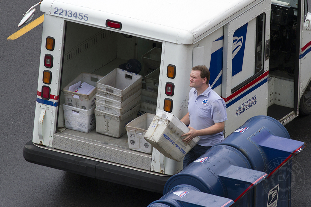 A United States Postal Service employee gathers mail bins outside the Columbia post office.