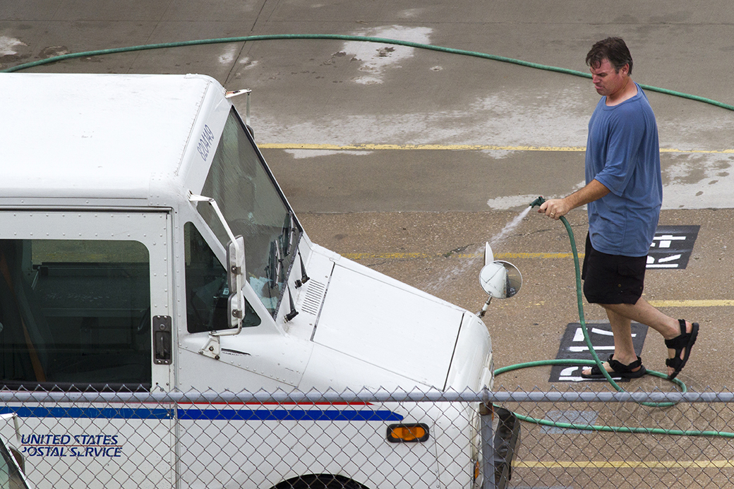 A man washes a U.S. Postal Service truck in Columbia, Mo.
