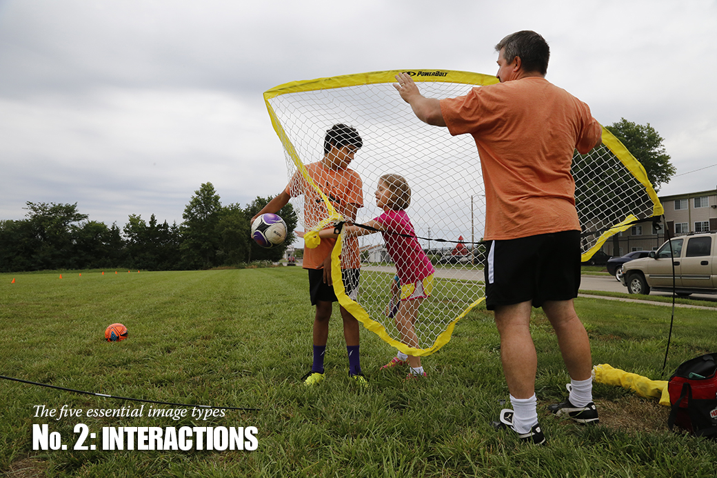 Ben Immel, 13, teases Juhad Belzer, 9, with a soccer ball while Heath Immel sets up a portable soccer net.