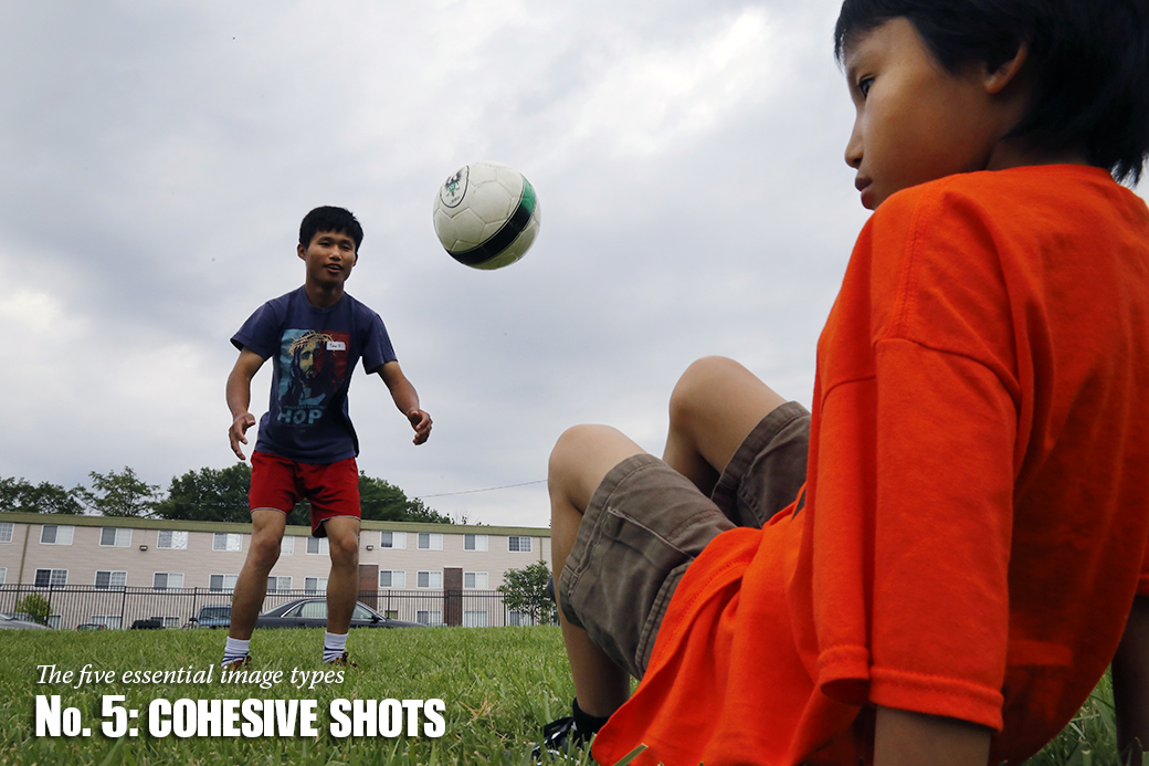 Taw Taw, a refugee from Burma, now known as Myanmar, left, helps Moe Eh Poe, 7, during a kicking drill at a field behind the Broadway Christian Church on Saturday, July 5, 2014.