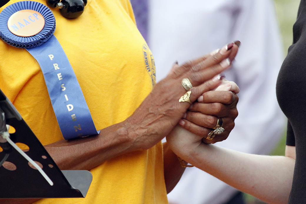 Missouri NAACP President Mary Ratliff grasps the hand of a Missouri Faith Voices affiliate during an NAACP rally in Columbia, Mo., on Aug. 21, 2014.