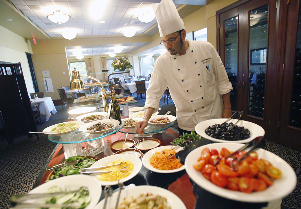 "Pliska ensures the day's buffet spread is in order on Oct. 22, 2014. ""I didn't have any formal training,"" Pliska said. ""I didn't go to culinary school."""