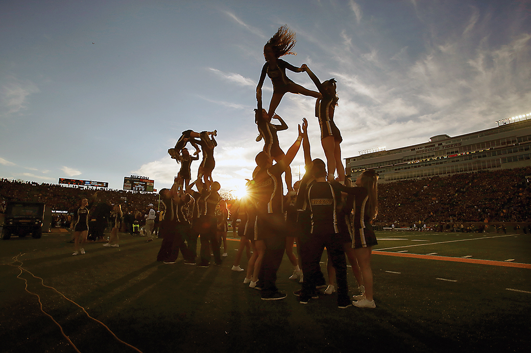 The sun sets on the MU Spirit Squad as it forms a pyramid during the third quarter of the Tigers football game against the Razorbacks at Memorial Stadium on Nov. 28, 2014. Metadata: f/16; 1/1000; ISO 1250; 18mm focal length
