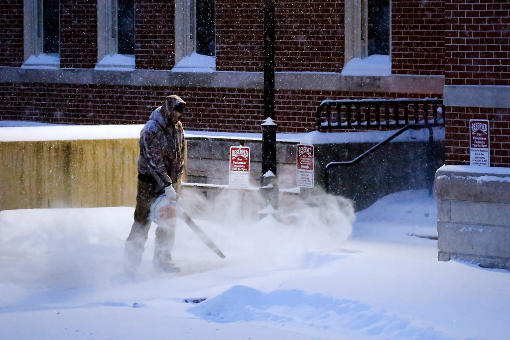An MU Campus Facilities employee uses a snowblower on the parking lot behind Pickard Hall on Monday morning. At 6 a.m., MU canceled classes and closed the university for the day.